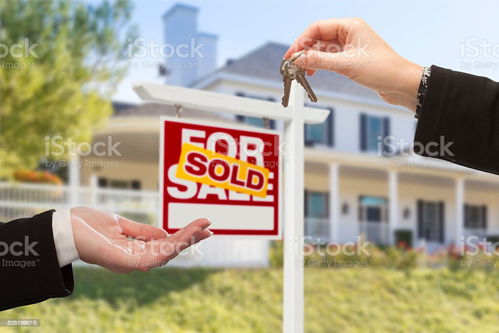 Sold Sign and Agent Handing Over Keys to New Home stock photo
