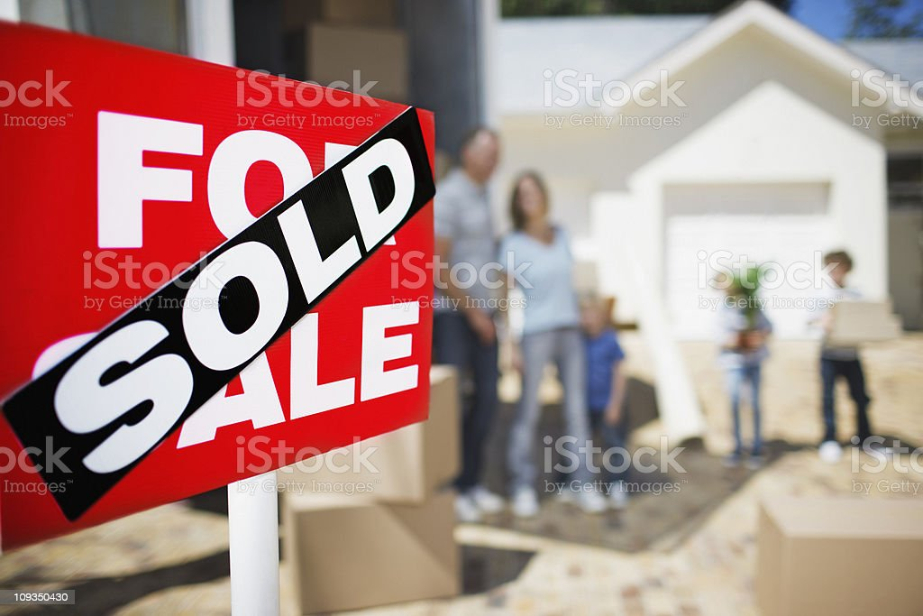 Sold sign on house with family in the background royalty-free stock photo
