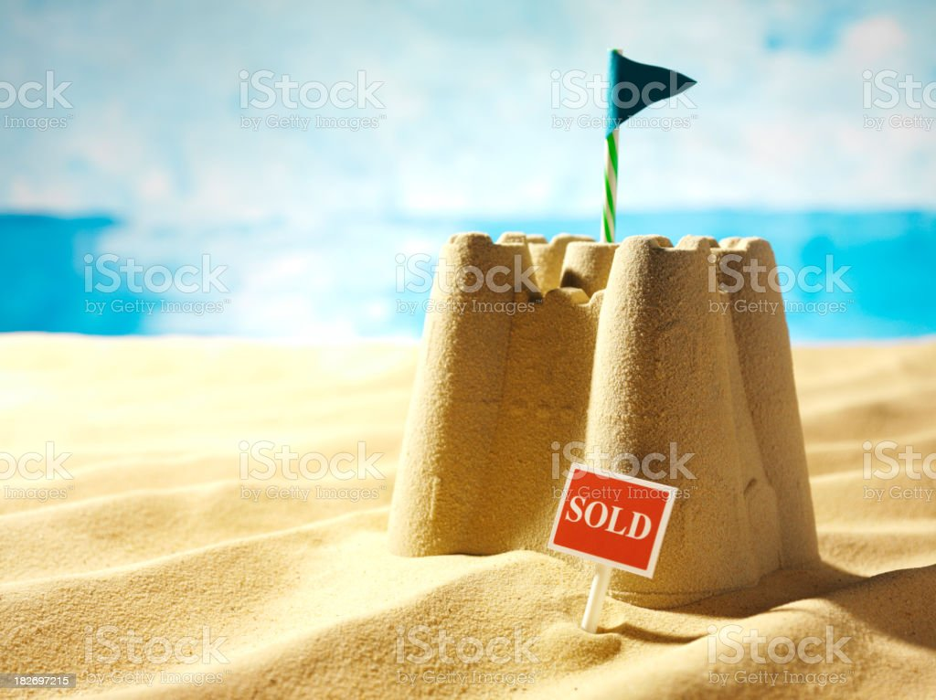 Sold Sign, Sea and a Sandcastle stock photo