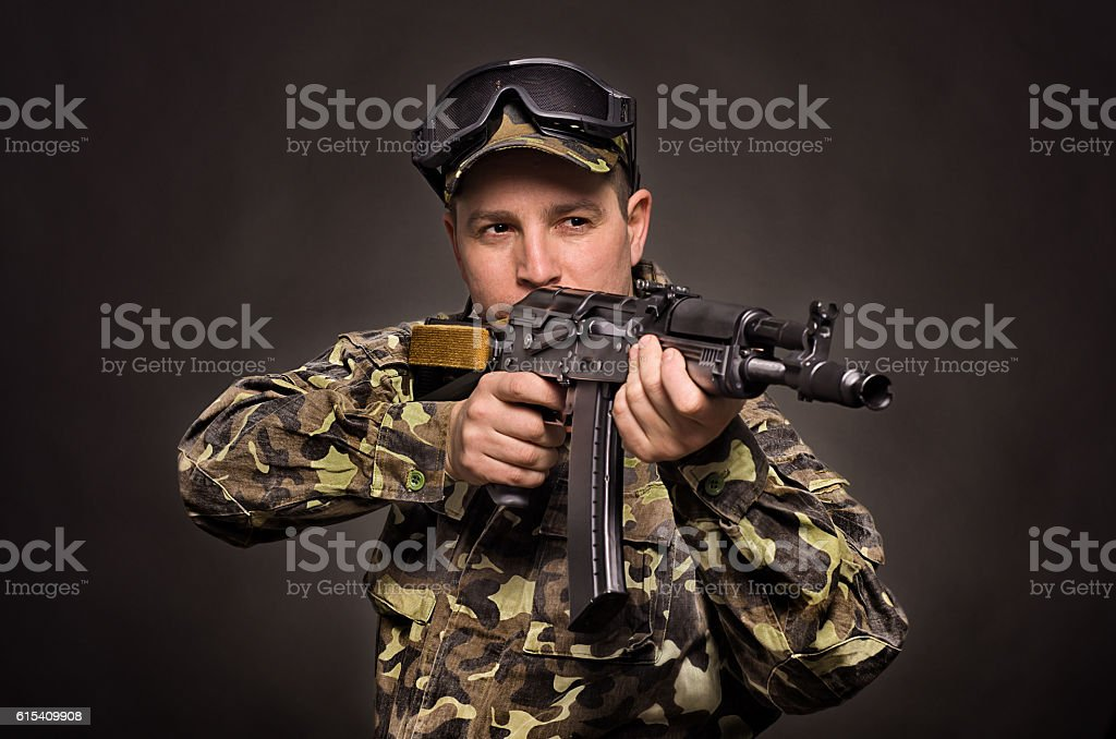 Soldier aiming a machine gun on a black background stock photo