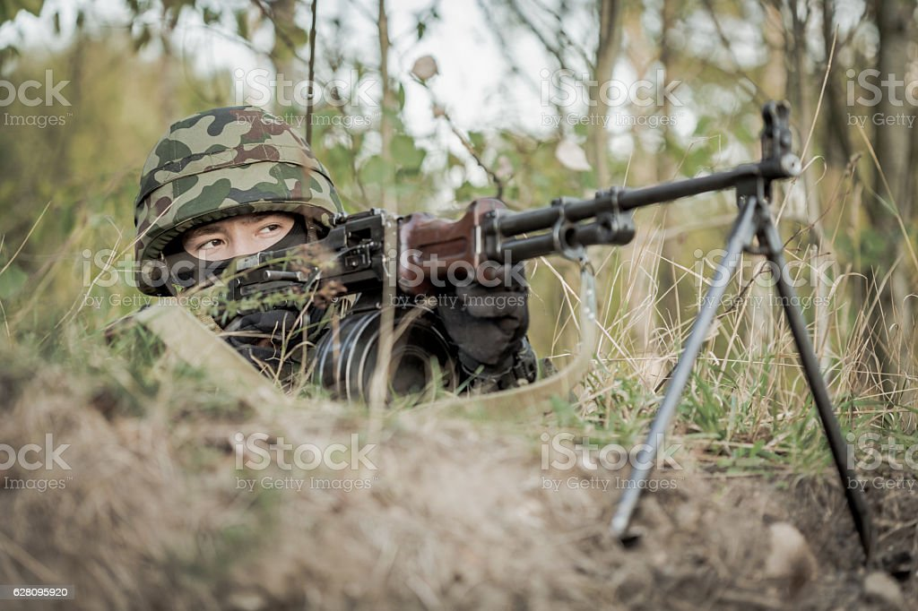 Soldier aiming from machine gun stock photo