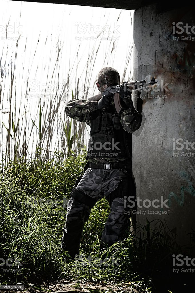 Soldier aiming his assault rifle under bridge stock photo