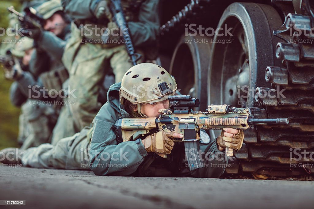 A soldier aiming his weapon and hiding by a tank stock photo
