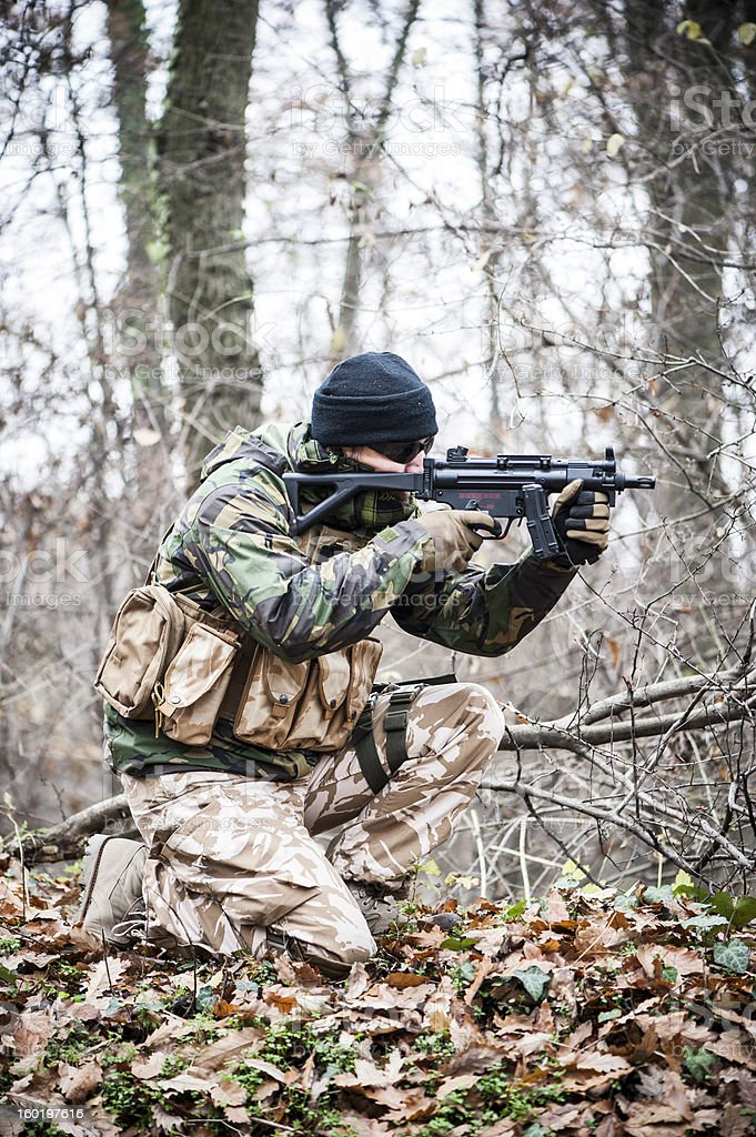 Soldier aiming in crouching position stock photo