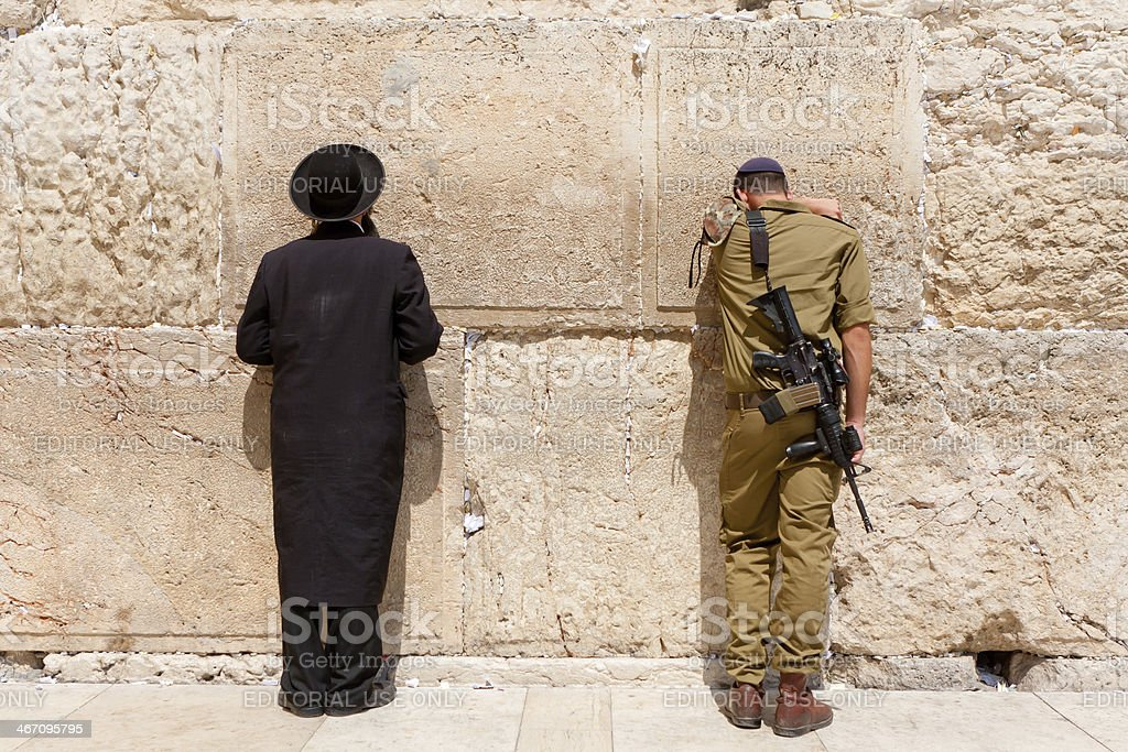 Soldier and Orthodox jews pray at the wailing all stock photo