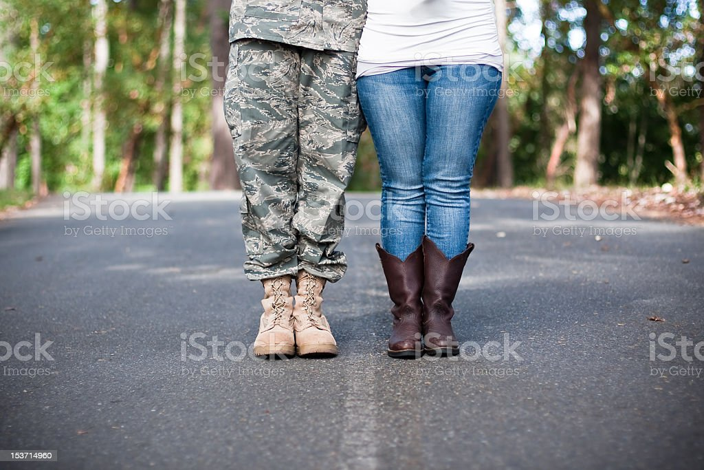 Soldier and wife standing on street separated by white line stock photo