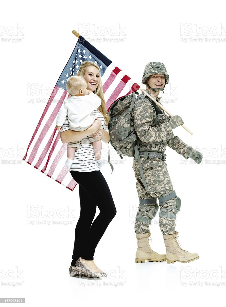 Soldier carrying an American flag with his wife royalty-free stock photo