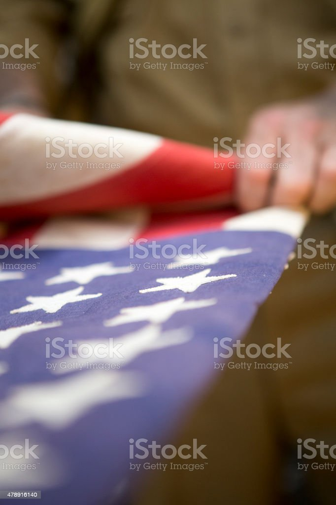 Soldier folding American Flag for fallen Warrior stock photo
