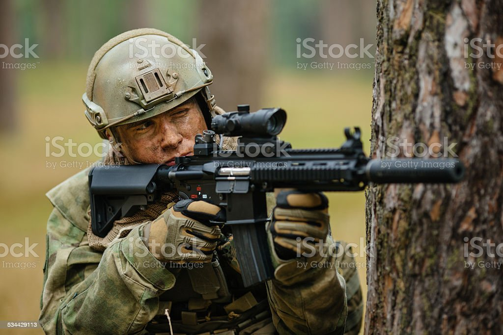 soldier holding a gun aiming through the scope stock photo