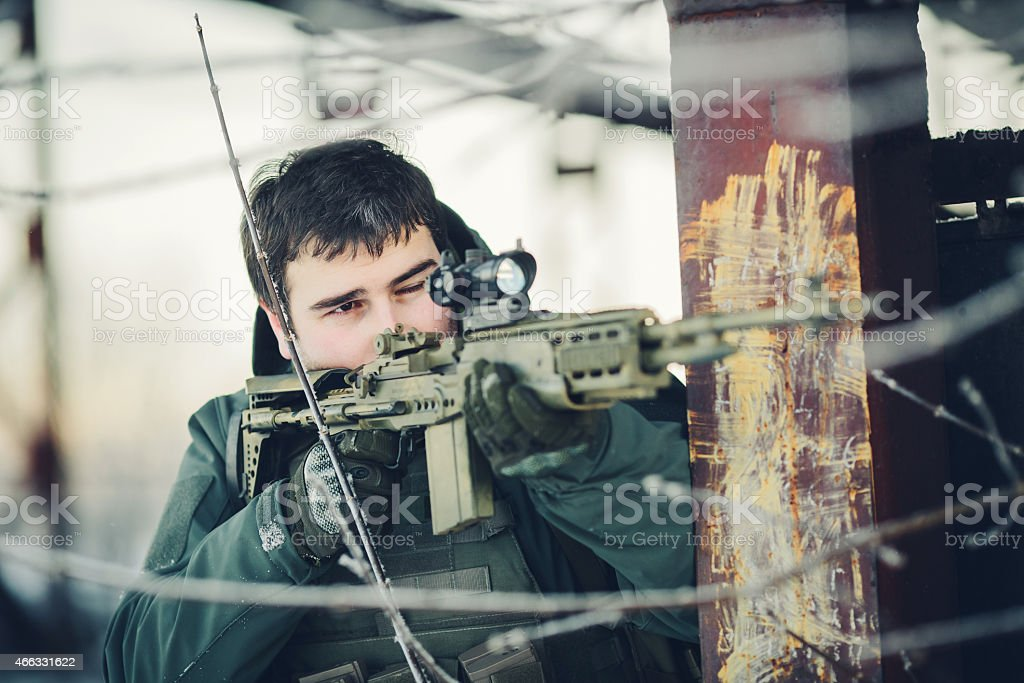soldier holding a gun and take aim at the enemy stock photo