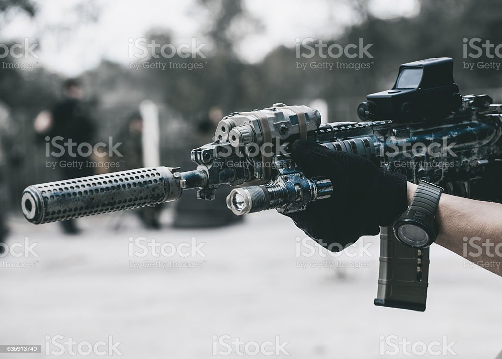 soldier holding a hand gun and takes aim for shot. stock photo