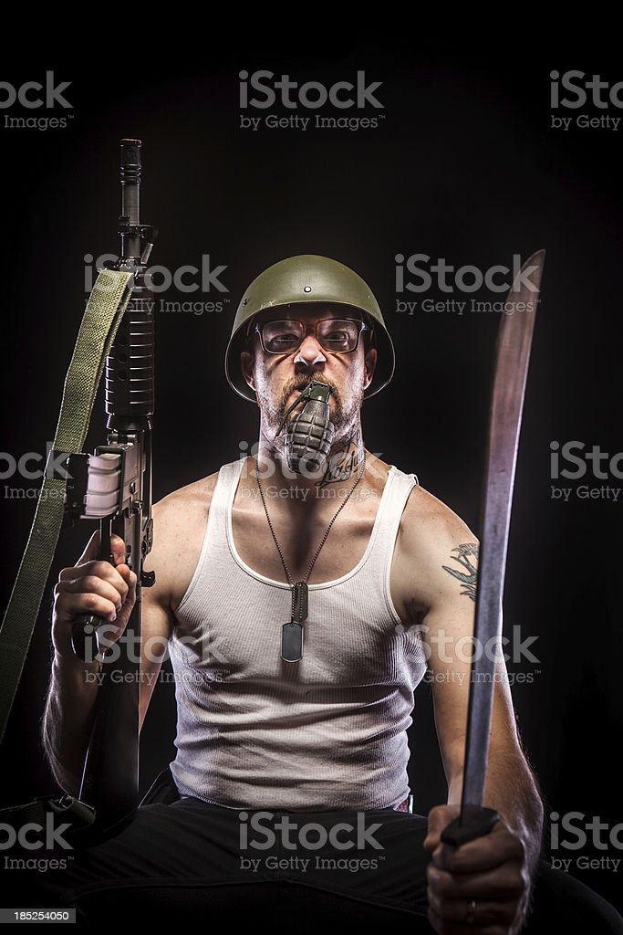 Soldier Holding Grenade in Mouth, Dog Tags, White Tank Top stock photo