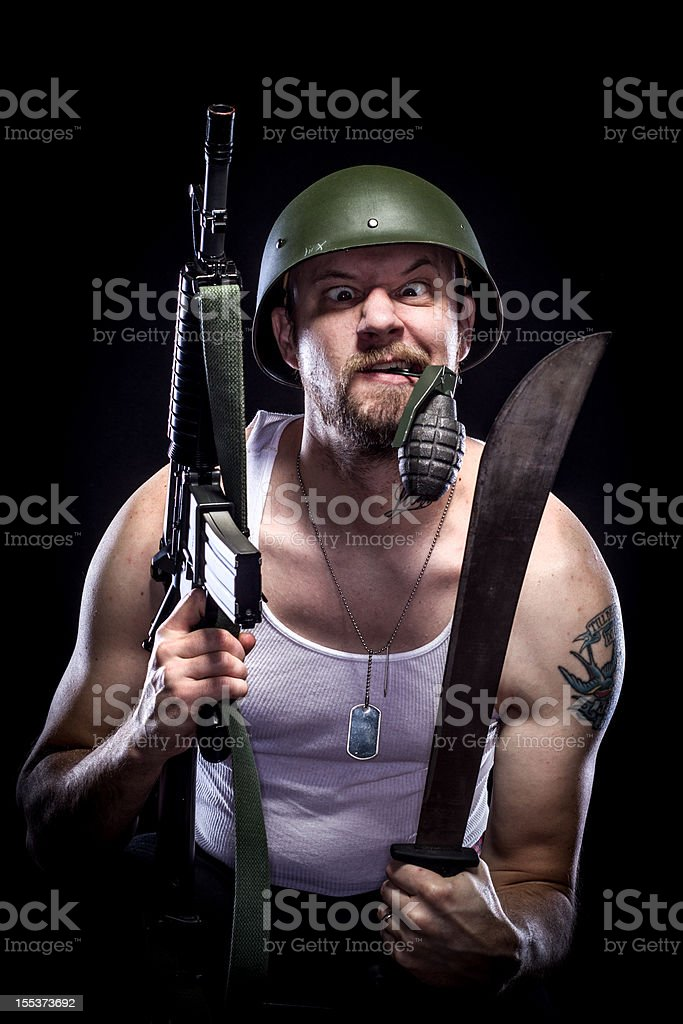 Soldier Holding Grenade in Mouth, Machete, M-16, Crazy Face stock photo