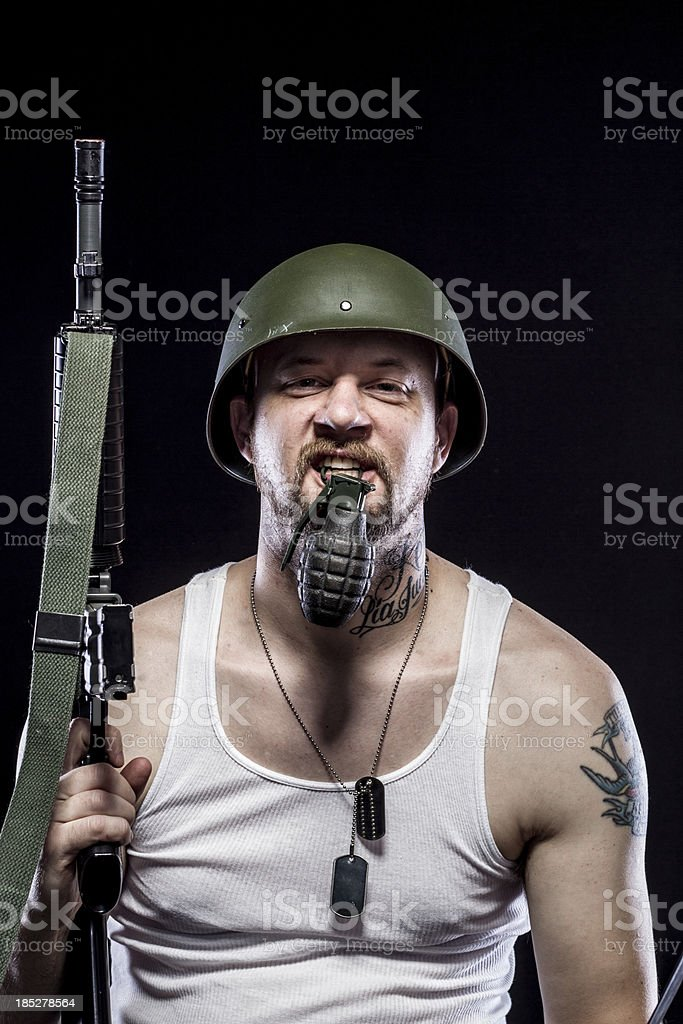 Soldier Holding Grenade in Mouth, Rifle, Dog Tags, Combat Helmet stock photo