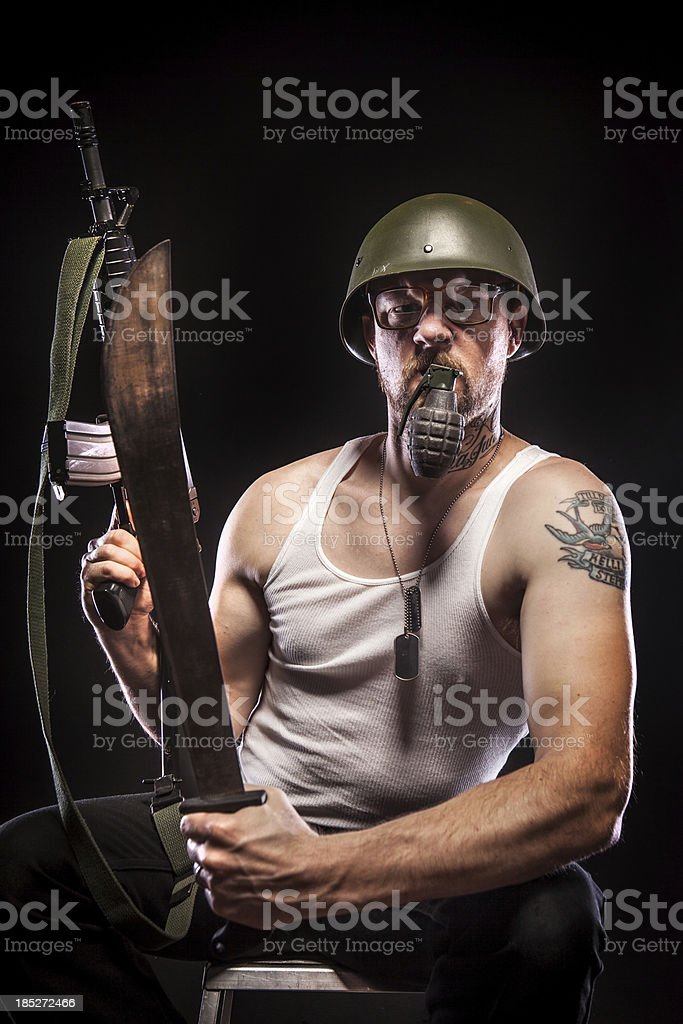 Soldier Holding Grenade in Mouth, Wearing Large Glasses stock photo