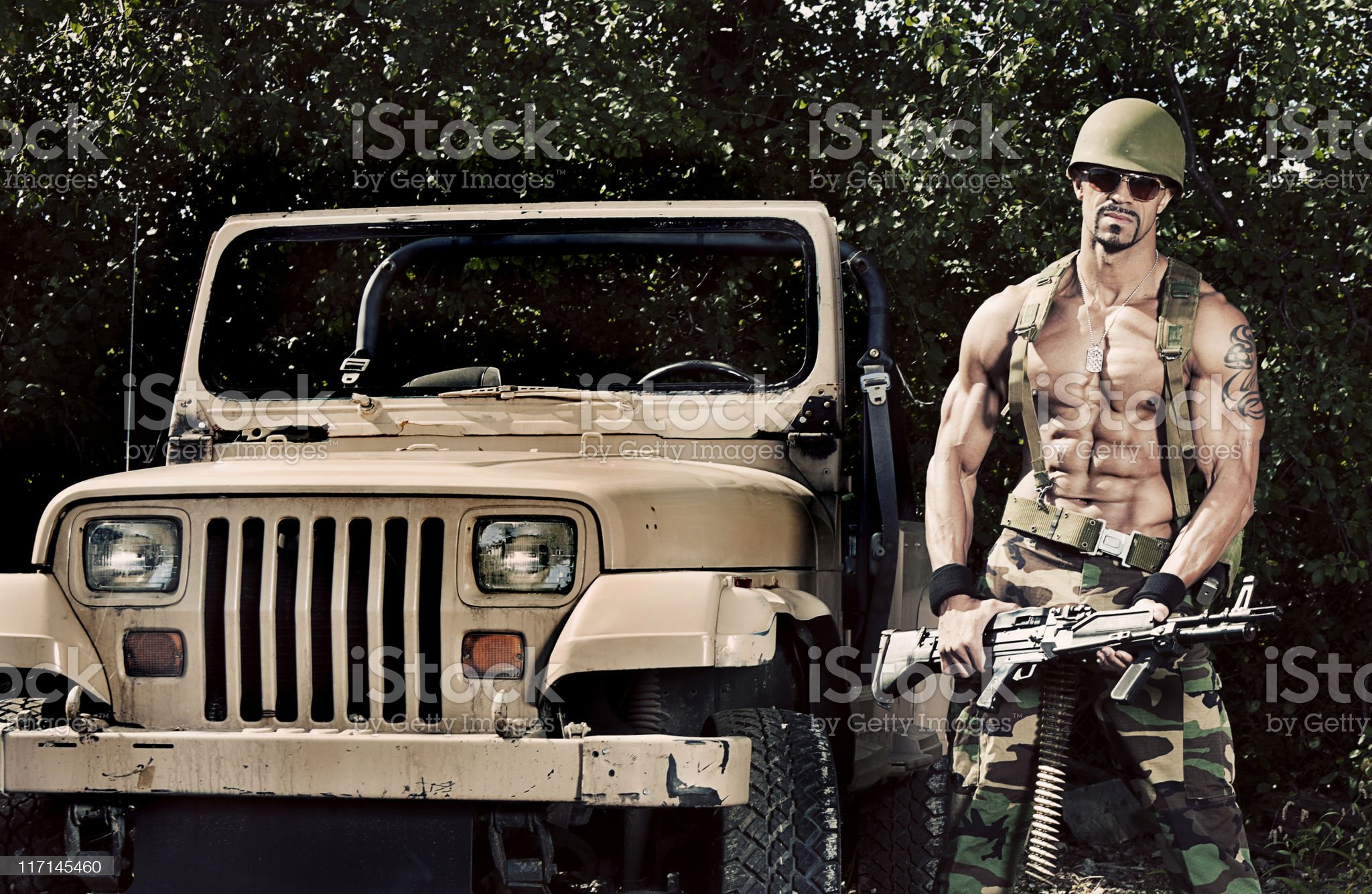 Soldier holding machine gun beside jeep royalty-free stock photo