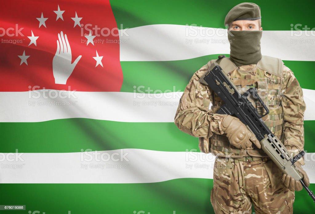 Soldier holding machine gun with flag on background series - Abkhazia stock photo