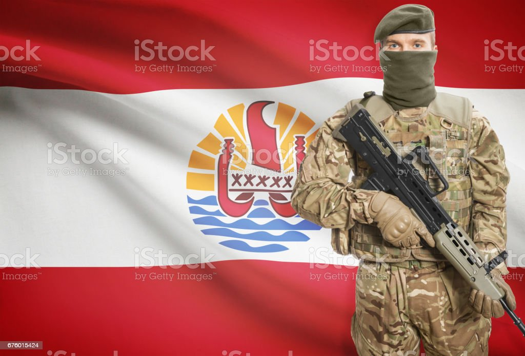 Soldier holding machine gun with flag on background series - French Polynesia stock photo