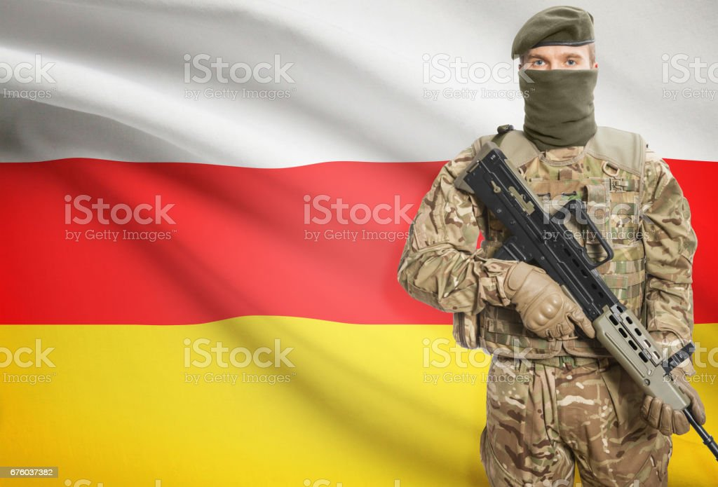 Soldier holding machine gun with flag on background series - South Ossetia stock photo