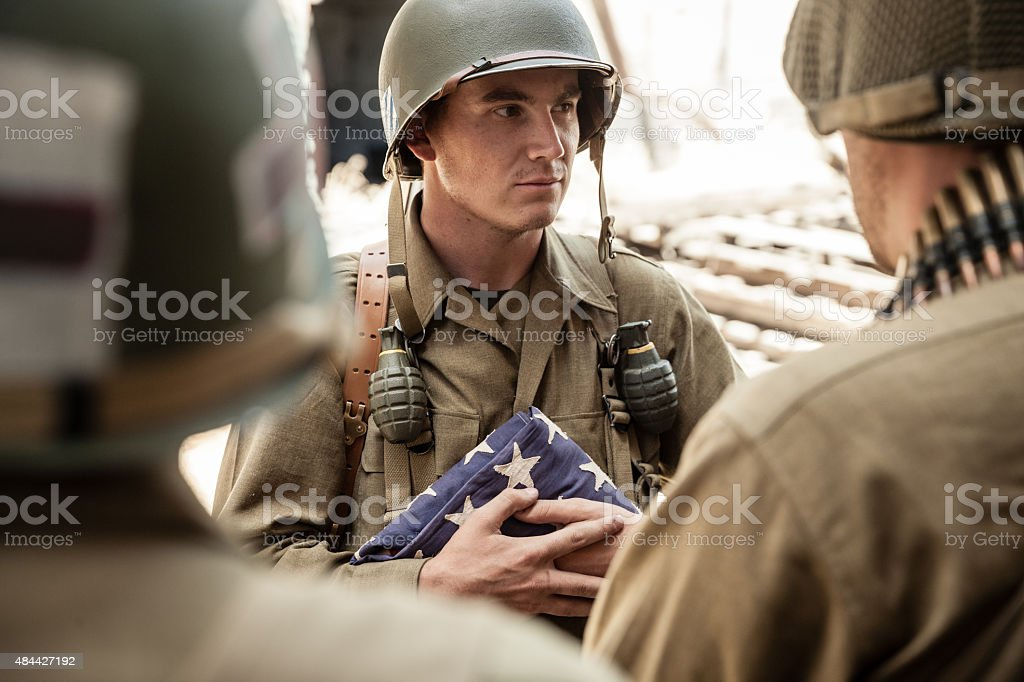WWII Soldier Holds Flag and Pays Respects with Platoon stock photo