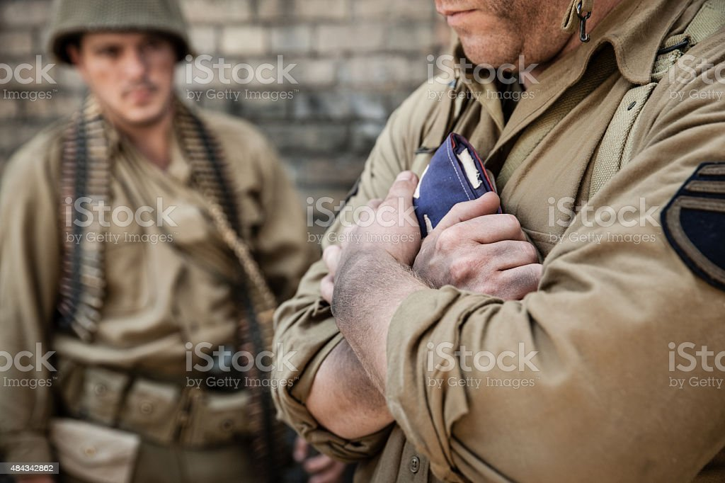 WWII Soldier Holds Flag Reverently stock photo