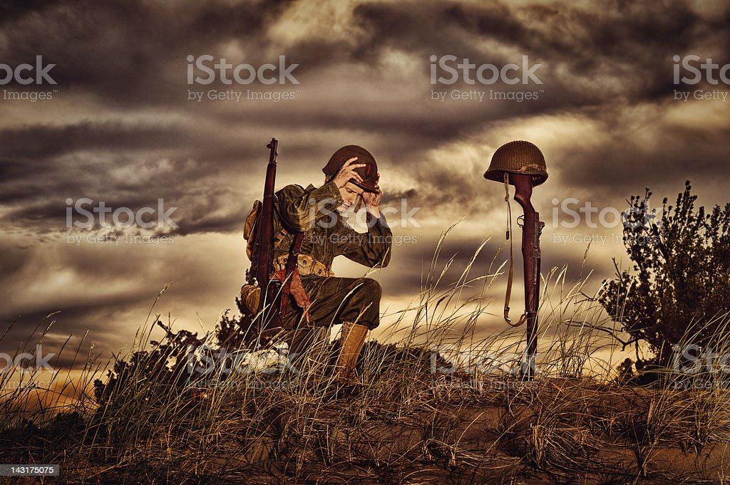 WWII Soldier Honoring His Fallen Friend stock photo