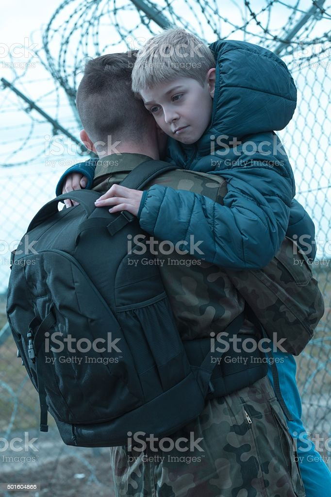 Soldier hugging little son stock photo