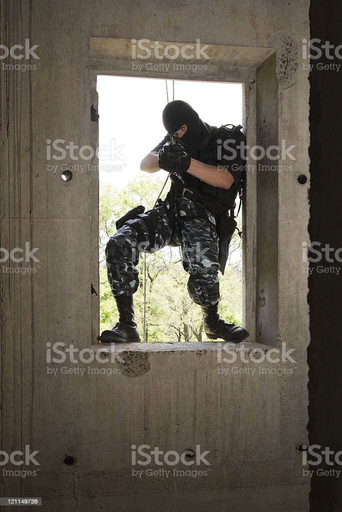 Soldier in black mask entering through the window royalty-free stock photo
