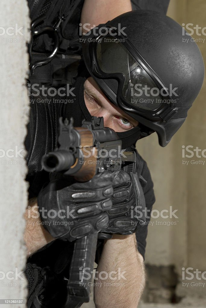 Soldier in black mask targeting with AK-47 rifle from cover royalty-free stock photo