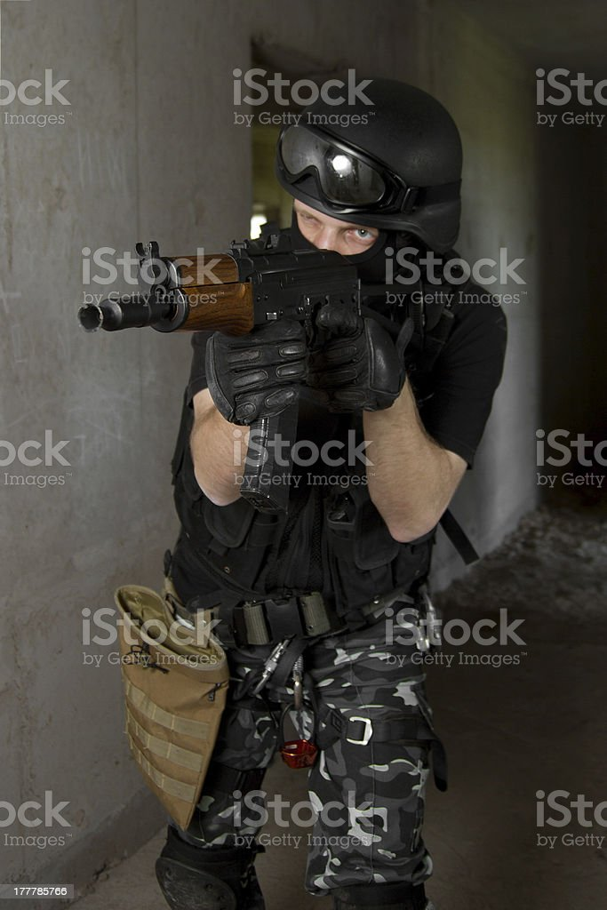 Soldier in black mask targeting with AK-47 rifle royalty-free stock photo