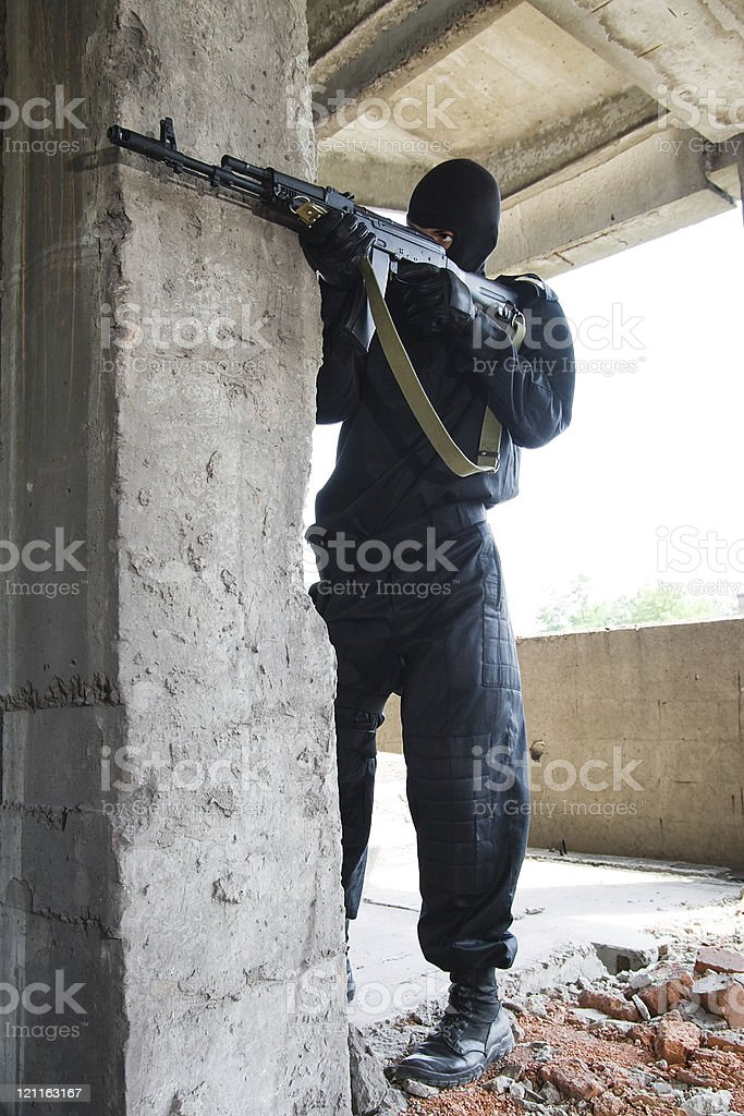 Soldier in black uniform with rifle royalty-free stock photo