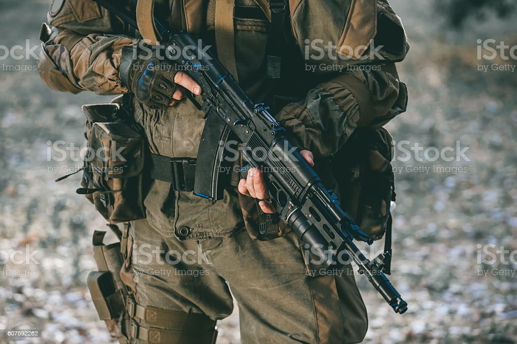 soldier in camouflage holding a gun. stock photo
