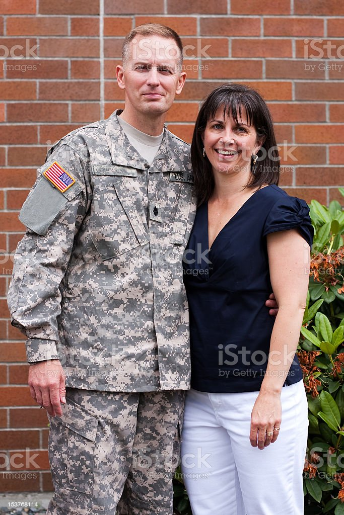 Soldier in fatigues with smiling wife beside brick building  stock photo