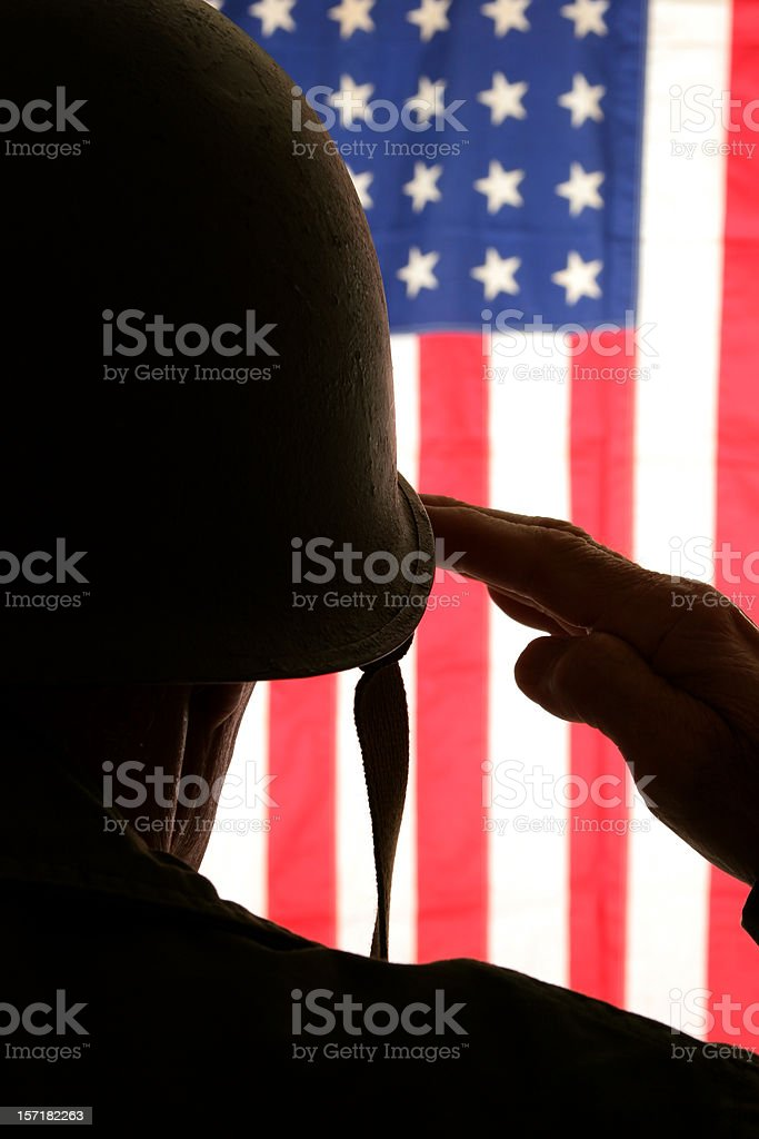 WWII soldier in field dress uniform saluting American flag royalty-free stock photo