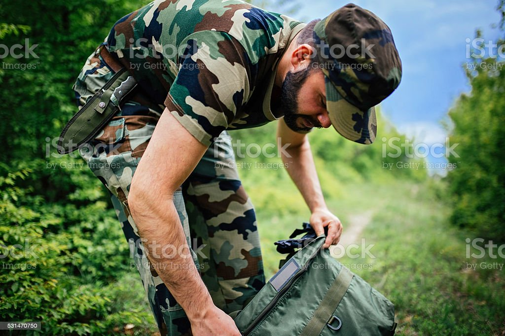 Soldier in forest packing stock photo