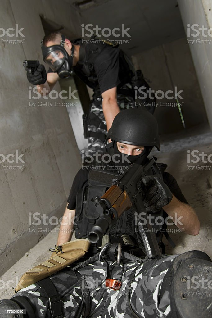 Soldier in gas mask saving his partner royalty-free stock photo
