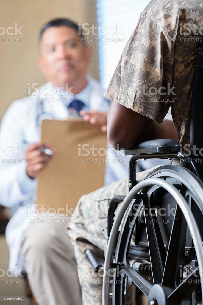 Soldier in wheelchair meeting with counselor or doctor stock photo