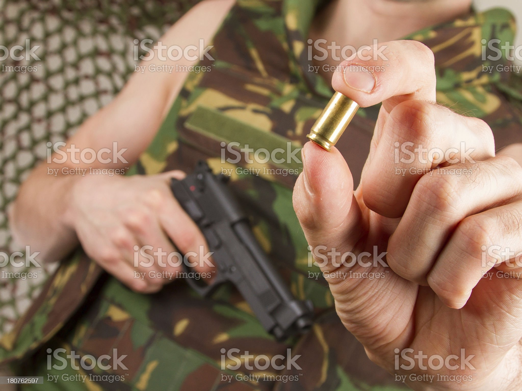Soldier is holding a gun and empty shell royalty-free stock photo