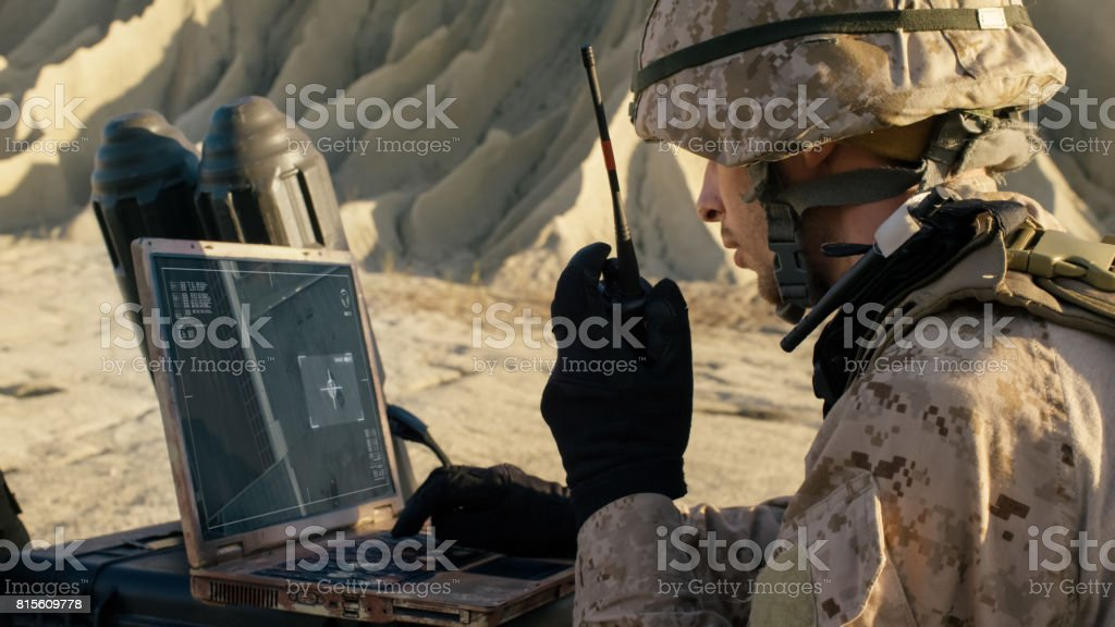 Soldier is Using Laptop Computer for Tracking the Target and Radio for Communication During Military Operation in the Desert stock photo