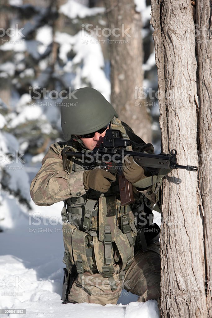 Soldier kneeling and aiming with rifle stock photo