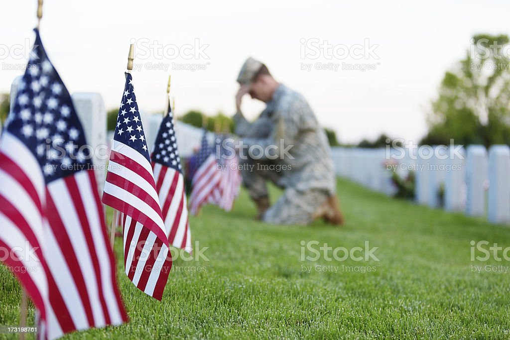 Soldier kneeling at grave stock photo