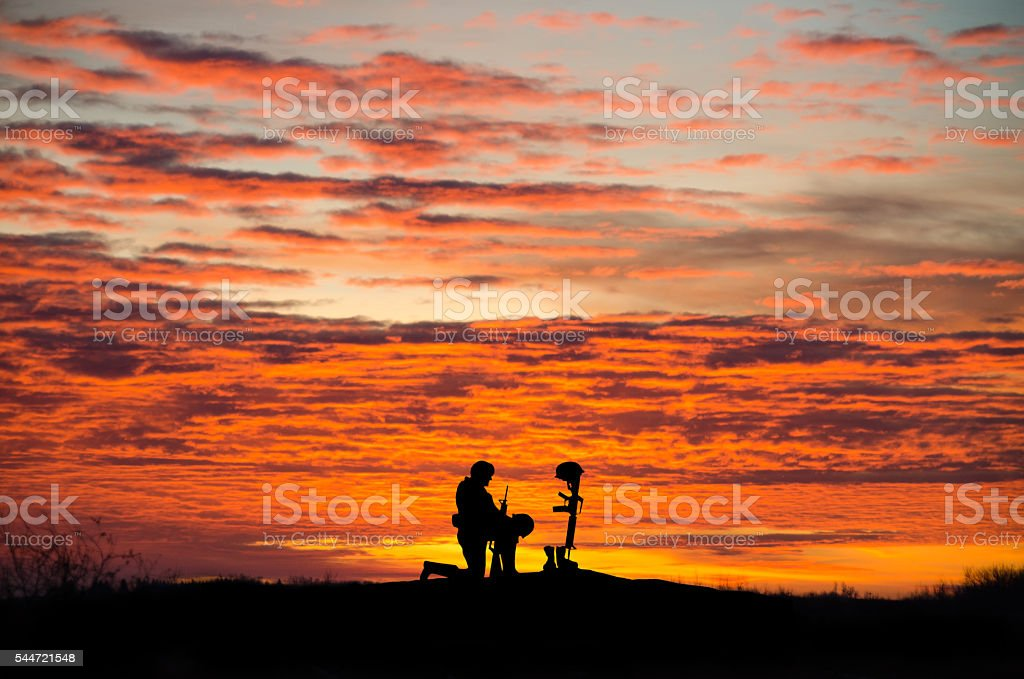 Soldier kneeling in front of a grave- sunset, copy space stock photo