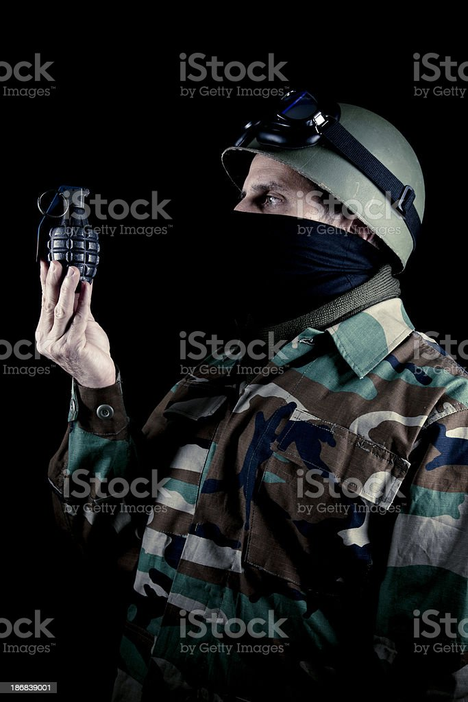 US soldier looking at grenade stock photo