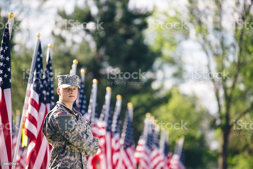 Soldier looking over his shoulder in fornt of American flags stock photo