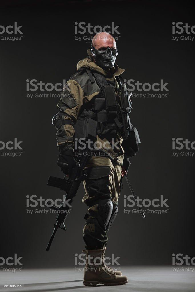 soldier man hold Machine gun on a  dark background stock photo