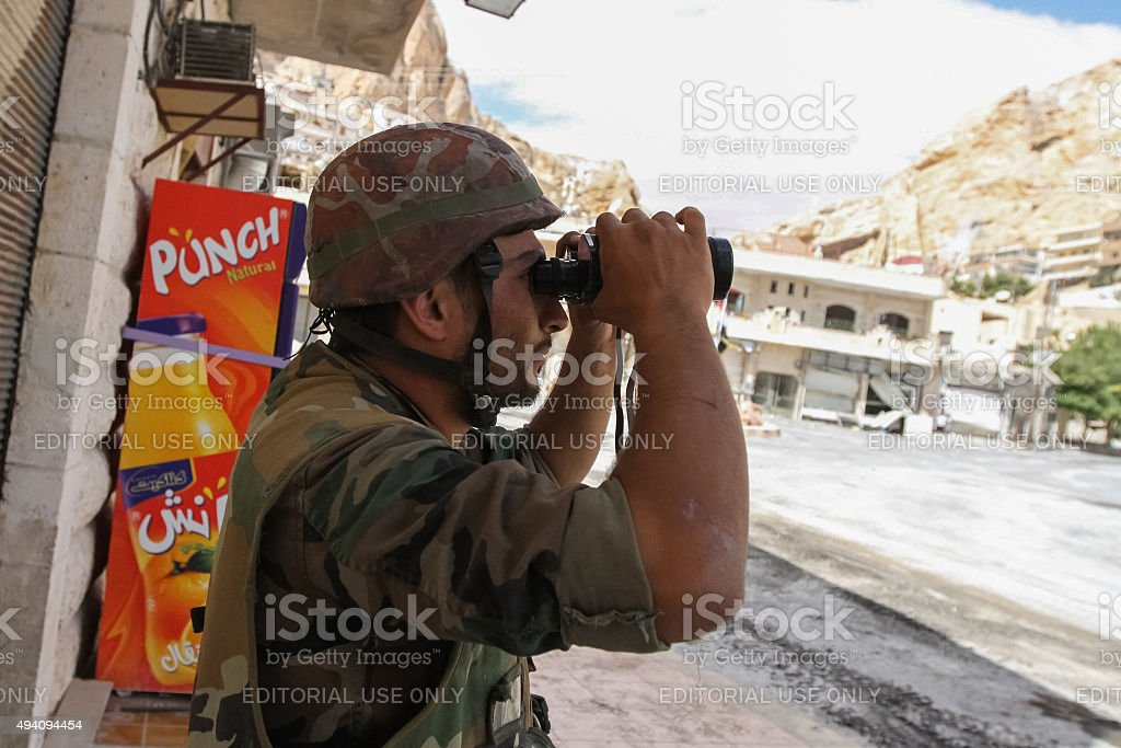 Soldier of the Syrian National Army is watching through binoculars stock photo