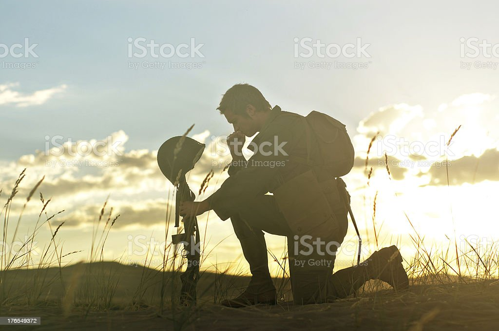 Soldier Praying for a Fallen Friend stock photo