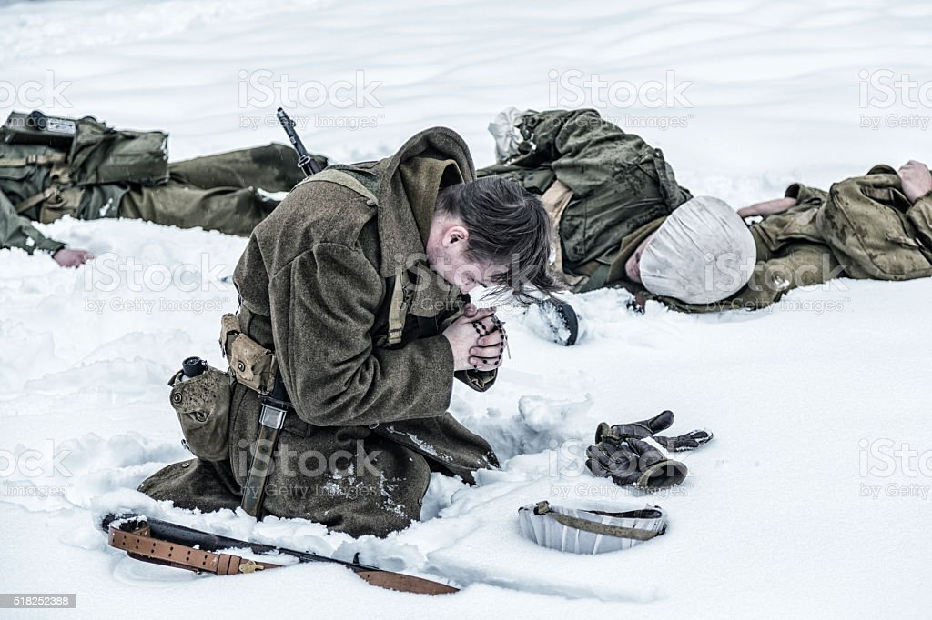 WWII Soldier Praying For Ambushed Comrade War Casualties stock photo