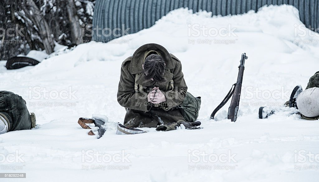 WWII Soldier Praying For Dead War Casualties stock photo