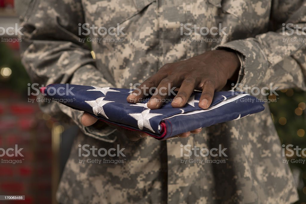 Soldier presenting an American Flag at Christmas royalty-free stock photo